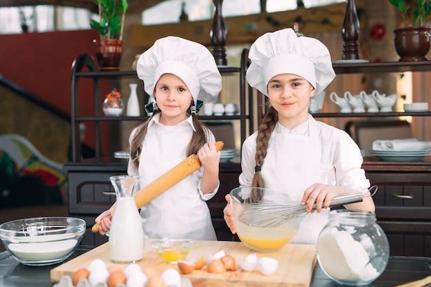 재미있는 여자 아이들이 부엌에서 반죽을 준비하고 있습니다.