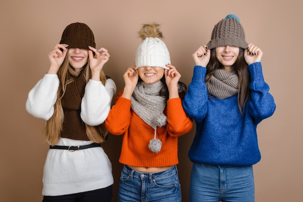 Funny girls in scarves pulled their hats on their eyes