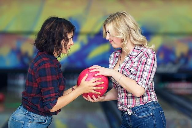 面白い女の子はお互いからボウリングのボールを奪う