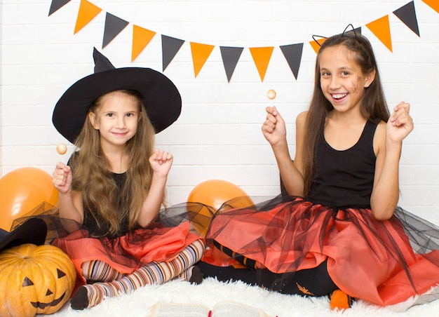 Funny girls in a witch costume for halloween with a pumpkin jack hold lollipops in their hands