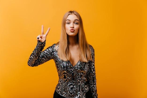 ピースサインとオレンジでポーズをとって面白い魅力的な女性。スパークルジャケットで魅惑的な盲目の女性の屋内の肖像画。