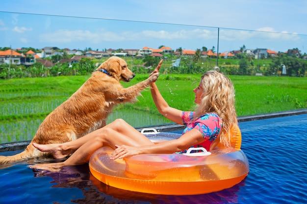 재미 있은 골든 래브라도 리트리버는 수영장에서 수영하는 행복 소녀에게 하이 파이브를 제공합니다. 럭셔리 빌라에서 수영장 파티를 즐기십시오.