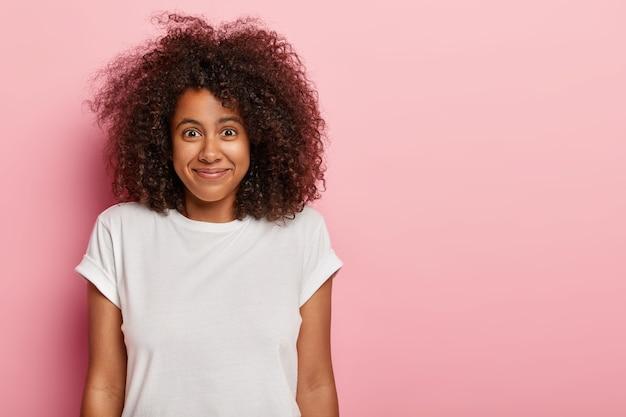 面白い格好良い巻き毛の女性のティーンエイジャーは、表情を喜ばせ、物事がどのように進んでいるかに満足し、素敵な驚きや良いニュースを喜んで、白いtシャツを着て、バラ色の壁にモデルを着ています