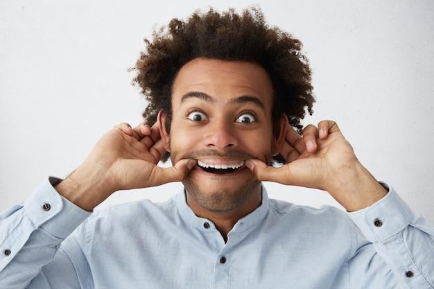 Забавный тупой молодой темнокожий мужчина с гримасой растягивает рот обеими руками