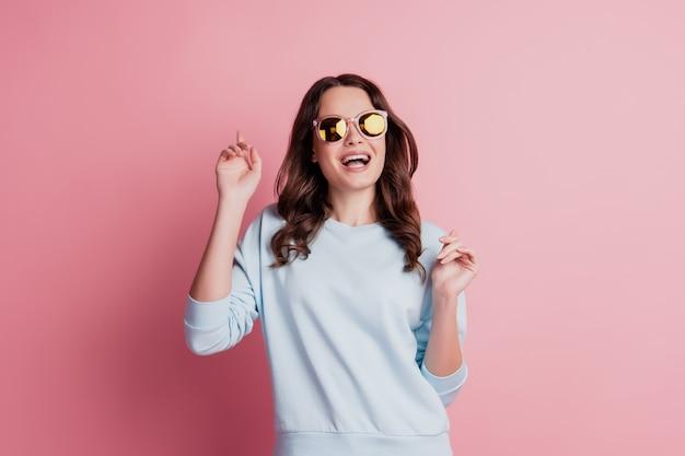 Забавные великолепные стильные солнцезащитные очки в женской одежде веселятся с открытым ртом беззаботным настроением на розовой стене