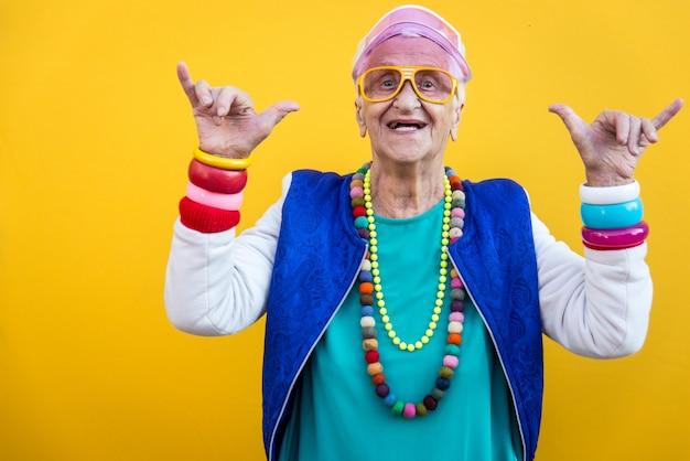面白い祖母の肖像画。 80年代スタイルの服。色付きの背景にトラップスターダンス。年功序列と高齢者についての概念