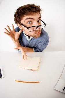 Смешно морщась бородатый мужчина в очках, сидеть офисный стол, надуться, сходит с ума на работе