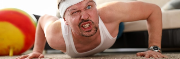 Funny grimacing man making push-ups home during coronavirus quarantine period portrait