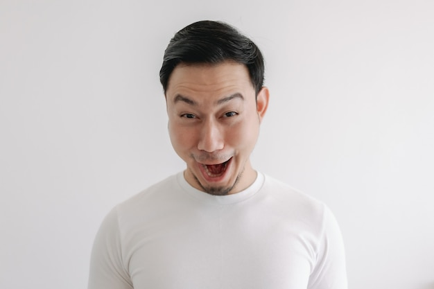 Funny grin smile face of man in white tshirt isolated on white wall