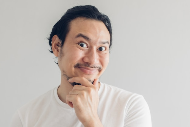 Funny grinning smile face of man in white t-shirt and grey background.