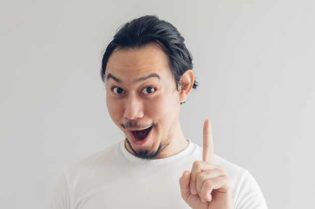 Funny grinning smile face of man in white t-shirt and grey wall.