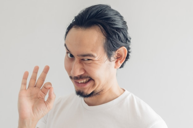Смешное ухмыляющееся лицо улыбки человека в белой футболке и сером фоне.
