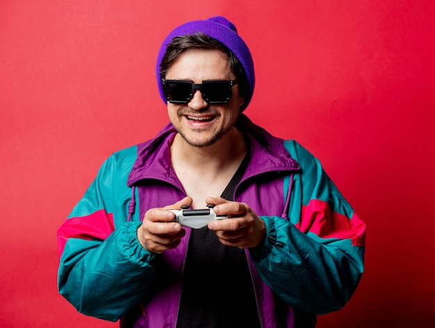 Funny guy in 80s style jacket and sunglasses hold game controller on red backgorund