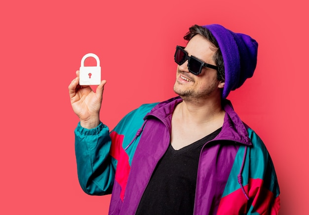 Funny guy in 80s style jacket and sunglasses hold lock symbol on red backgorund