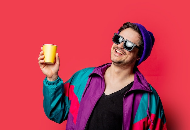 Funny guy in 80s style jacket and sunglasses holds paper cup on red backgorund