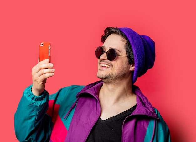 Funny guy in 80s style jacket and sunglasses make selfie on red backgorund