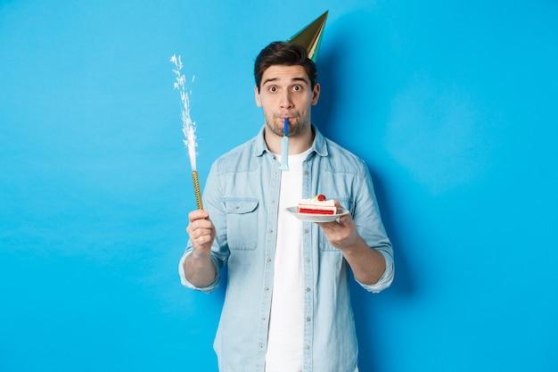 Funny guy celebrating birthday, holding b-day cake, firework and wearing party hat, standing over blue wall