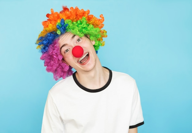 Funny guy in a clown costume on a blue
