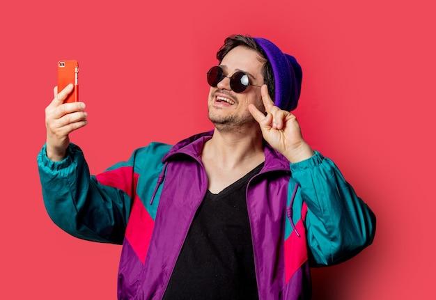 Забавный парень в куртке в стиле 80-х и солнечных очках делает селфи на красном фоне