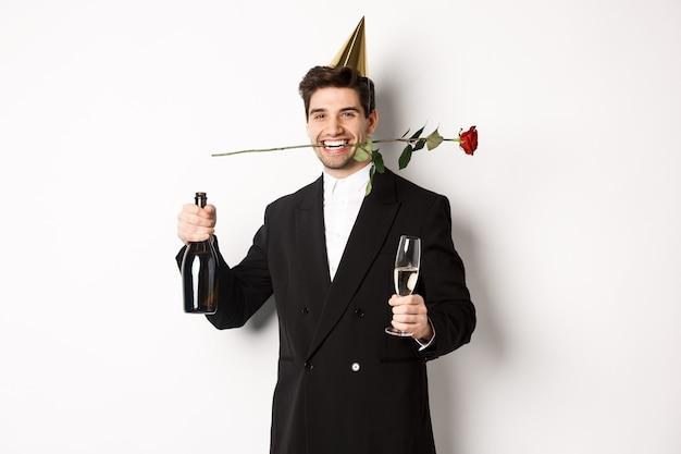 トレンディなスーツを着た面白い男、祝ってパーティーを開き、白い背景の上に立って、歯とシャンパンでバラを持っています。