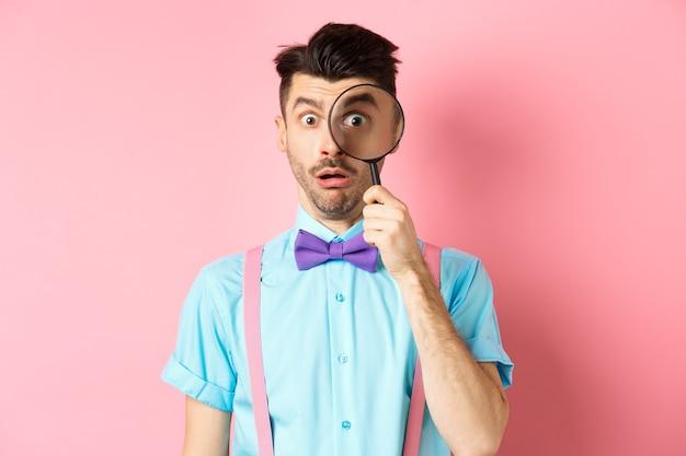 面白い男は、ピンクの背景の上に立って、何か面白いものを見て、驚いた顔で虫眼鏡を通して見ます。