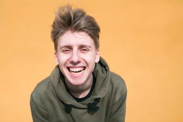 A funny guy smiles against on a orange wall.