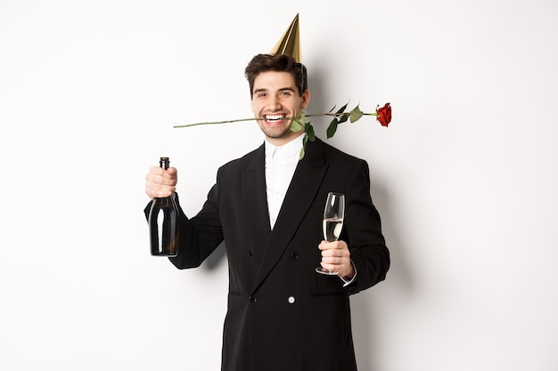 Funny guy in trendy suit, celebrating and having a party, holding rose in teeth and champagne, standing over white background.