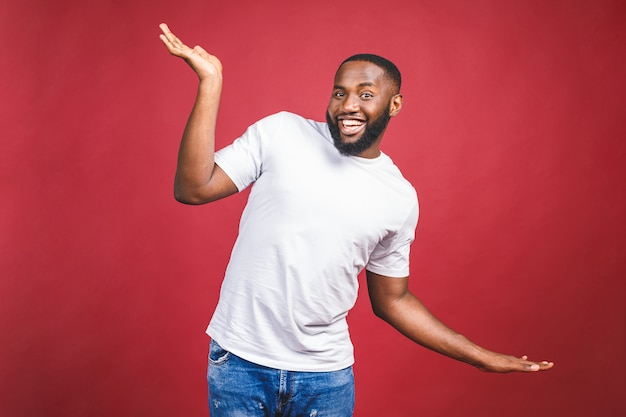 Funny guy in white t-shirt jumping and looking at camera. studio portrait of emotional african male model posing on red background.