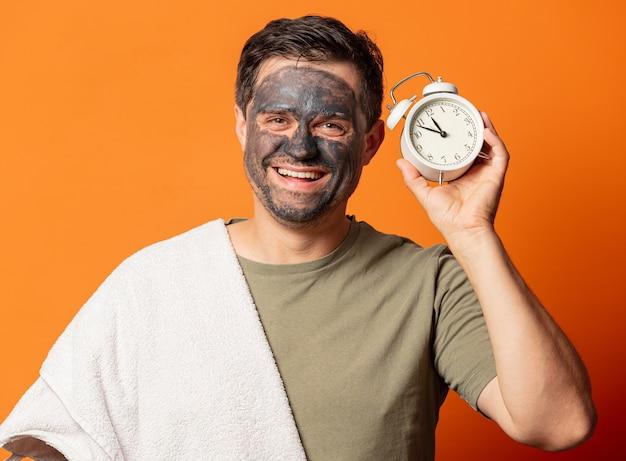 彼の顔に化粧マスクとオレンジ色の目覚まし時計を持つ面白い男