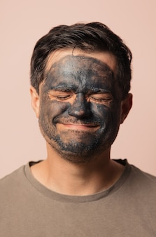 Funny guy with a cosmetic mask on his face on pink
