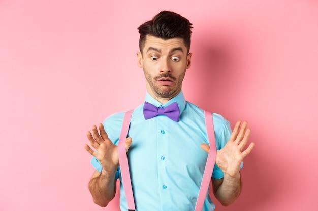 Забавный парень с усами и галстуком-бабочкой поправляет подтяжки и смотрит вниз с растерянным и удивленным лицом, стоящий поверх розового.