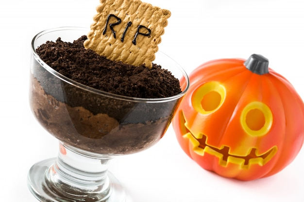Funny halloween chocolate mousse with tomb cookie and halloween pumpkin isolated on white