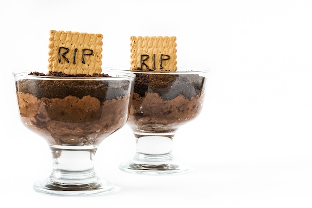 Funny halloween chocolate mousse with tomb cookie isolated on white copy space