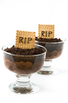 Funny halloween chocolate mousse with tomb cookie isolated on white