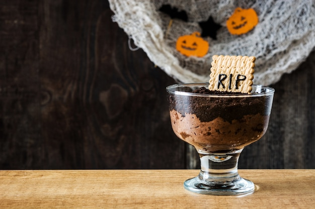 Funny halloween chocolate mousse with tomb cookie and spiders on wooden table copy space