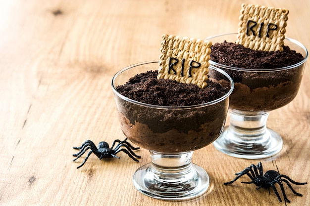 Funny halloween chocolate mousse with tomb cookie and spiders on wooden table