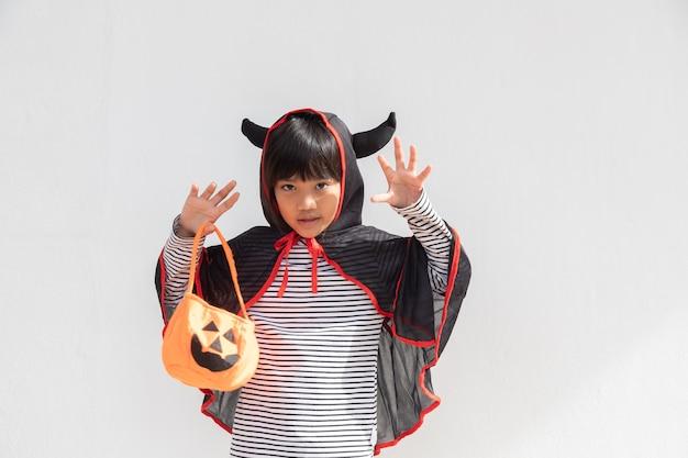 재미있는 할로윈 아이 개념, 할로윈 의상을 입은 귀여운 소녀, 흰색 바탕에 주황색 호박 유령을 들고 있는 무서운