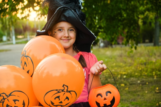 Забавная девочка ребенка хэллоуина с косметикой на лице в карнавальных костюмах на открытом воздухе.
