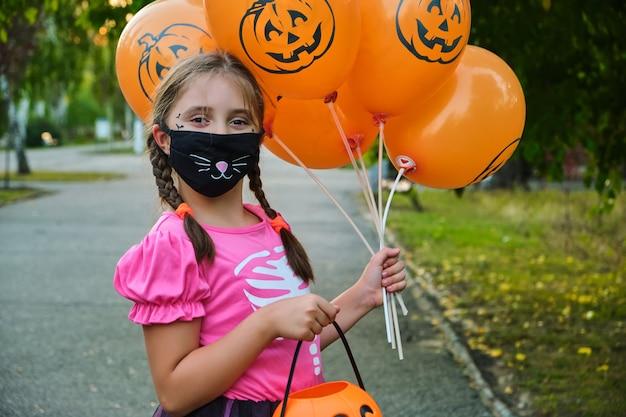 保護マスクで面白いハロウィーンの子供。屋外でカーニバルの衣装を着た女の子。
