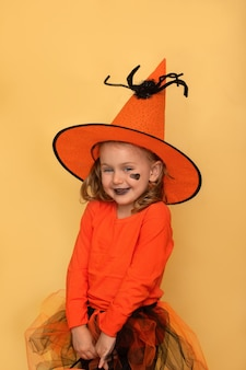 Funny halloween party kid concept smiling child girl in halloween orange witch costume and hat