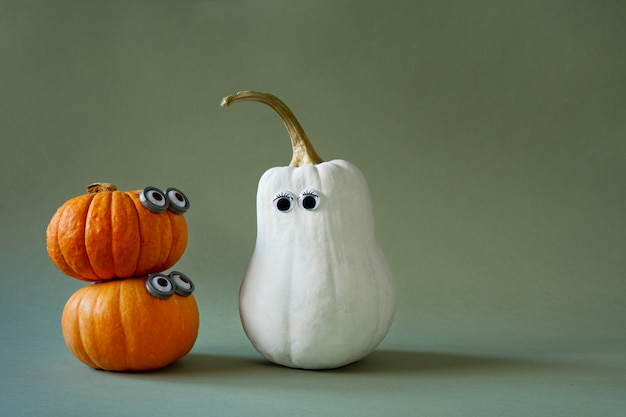 Funny halloween pumpkins with googly eyes on green