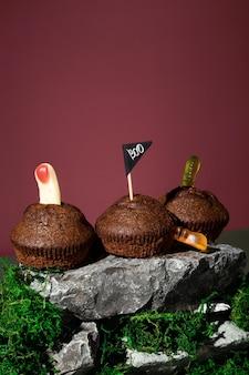 Забавный пейзаж хэллоуина. ужасные угрозы. кексы с желейными червями и пальчиками стоит на камнях и мхе