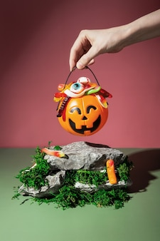Funny halloween scenery. trick or treat. pumpkin jack filled with various creepy sweets stands on stones and moss. woman hand holds basket