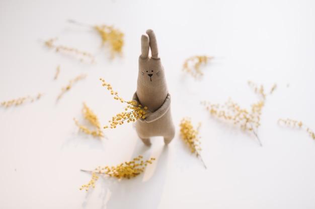 Забавная игрушка кролик кролик ручной работы держит желтые цветы пасхальную концепцию