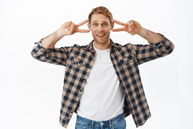Funny handsome adult man dancing, showing peace v-sign and smiling, stay positive, cheer you up, fool around and showing fun faces, standing over white wall