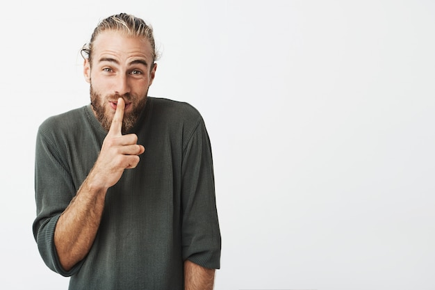 Funny handsome bearded man making hush hand gesture asking for silent