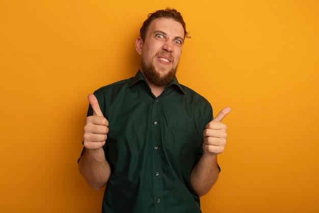 오렌지 벽에 고립 된 두 손의 재미있는 잘 생긴 금발 남자 엄지 손가락