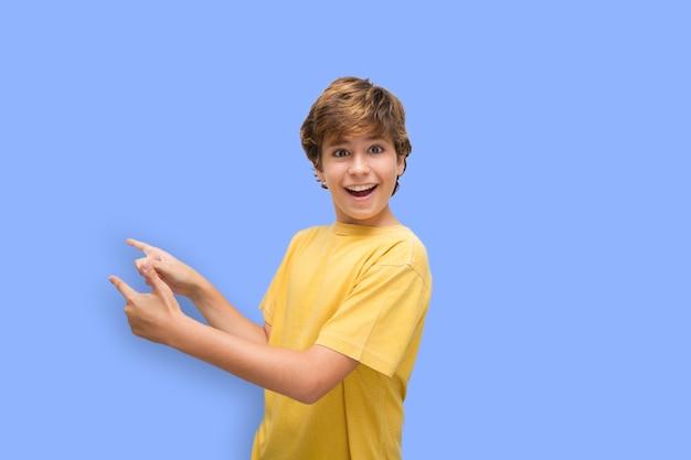 그의 손으로 뭔가 재미있는 제스처를 만드는 재미있는 잘 생긴 소년 몬스트란도