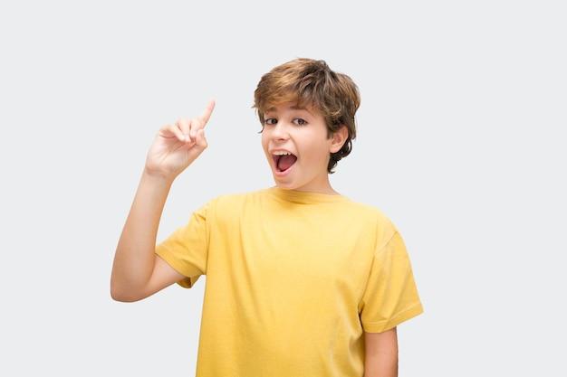 다른 배경을 가진 승인의 제스처를 만드는 재미있는 잘 생긴 소년