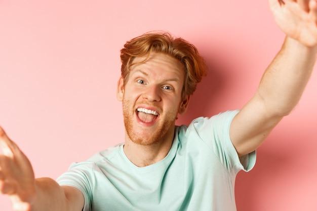 셀카를 찍는 우스꽝스러운 빨간 머리 남자, 카메라를 잡기 위해 손을 뻗고 행복하게 웃고, 스마트폰에서 보고, 분홍색 배경 위에 서서